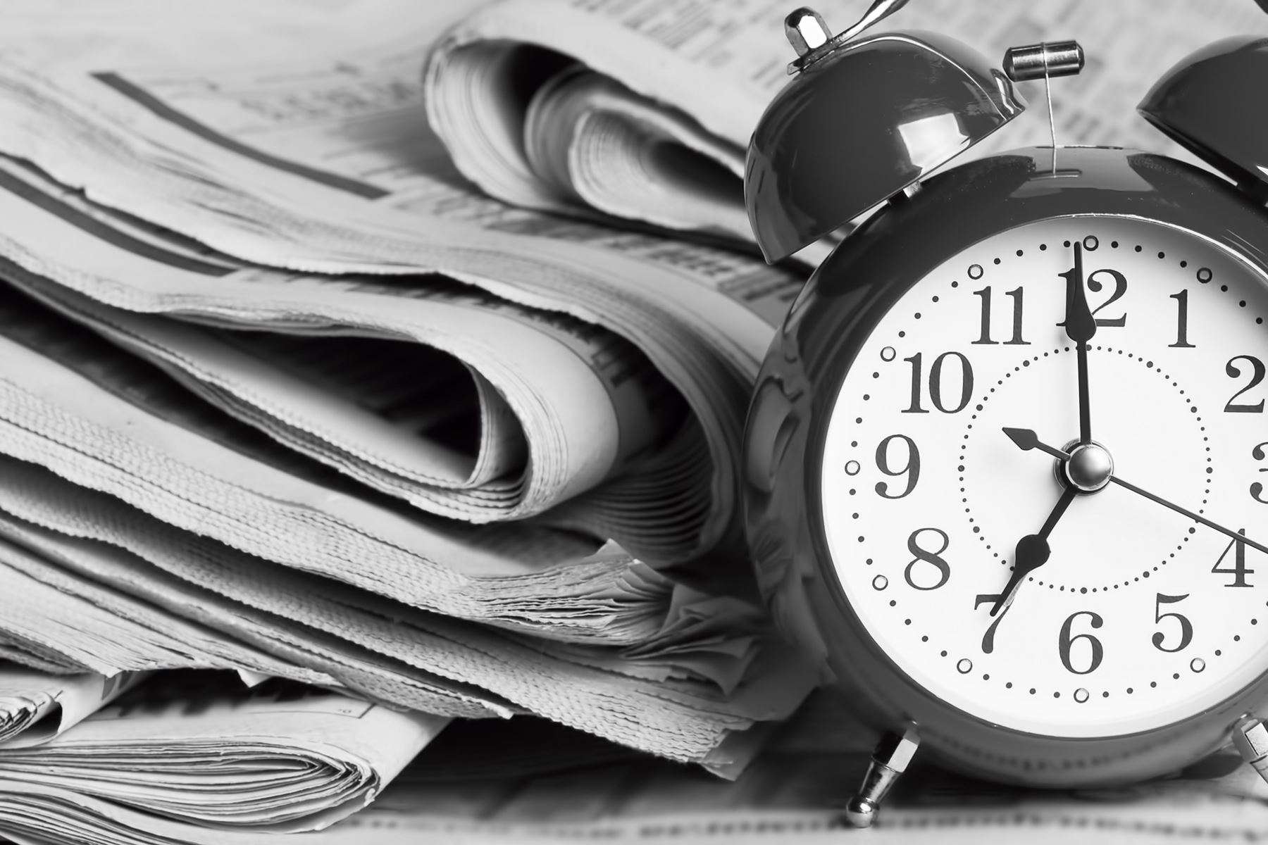 Alarm clock sitting next to a stack of news papers